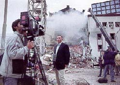 [CNN's Brent Sadler reports in April in front of the demolished Serb Radio and Television headquarters, one month after the first attack was aborted.]