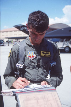 [Bandit #451 Hoyt Whetstone of the 7th FS signing a flight log. (ACC)]