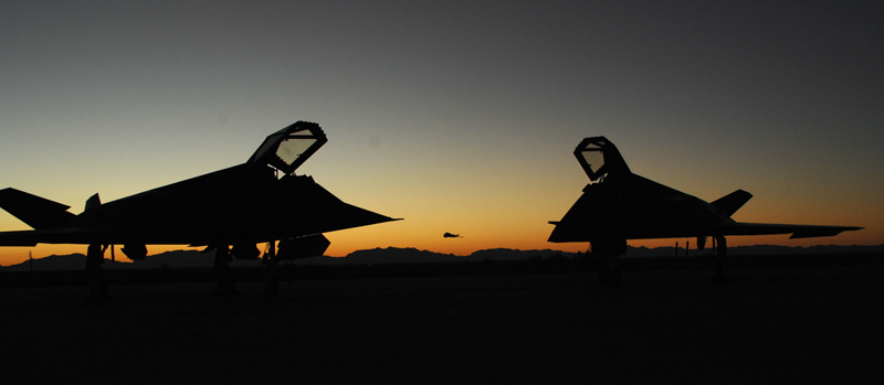 [Two F-117A Nighthawk sit on the Holloman flightline as another F-117A takes off into the sunset. (U.S. Air Force photo/ Airman 1st Class Heather Stanton)]